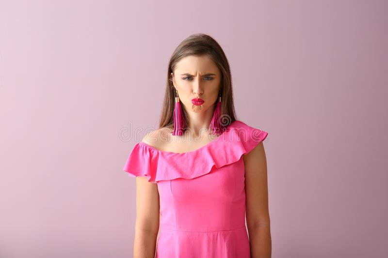 Beautiful offended young woman on color background stock image