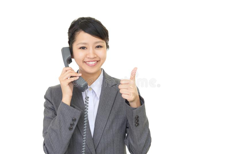 Business woman with a phone. A beautiful office lady talking on the phone royalty free stock image