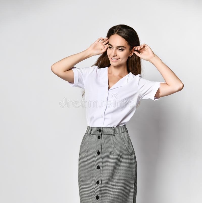 Beautiful woman office manager posing in a new casual white blouse and classic straight dark skirt. Beautiful office manager looks away raising his hands up in a stock images