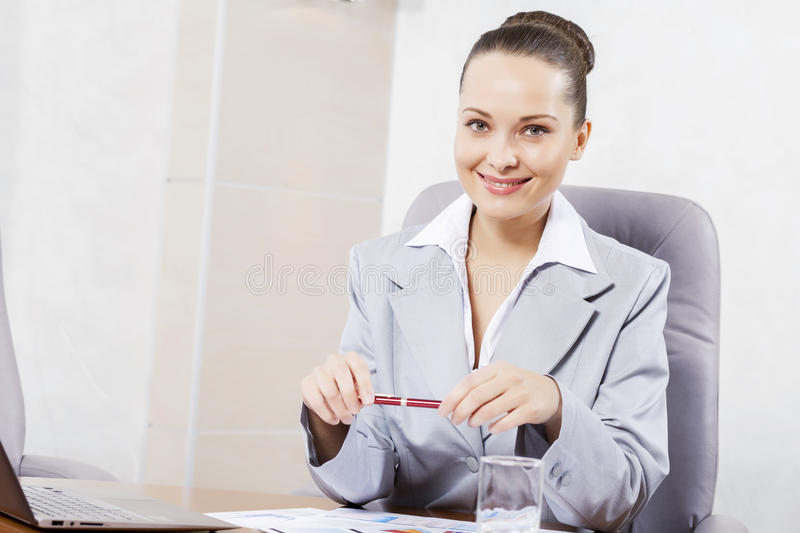 Beautiful office manager. Portrait of businesswoman with laptop working at her office royalty free stock photography