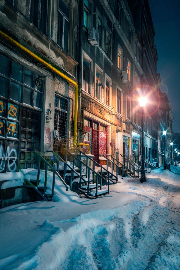 Beautiful old alley covered with snow in the winter with old buildings shot in the night well illuminated by street lamps stock photo