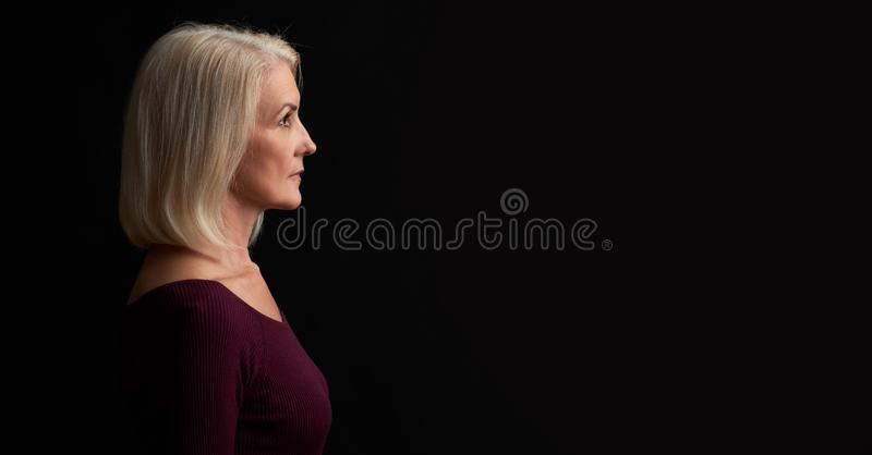 Beautiful old blonde woman profile. Isolated on black stock photo