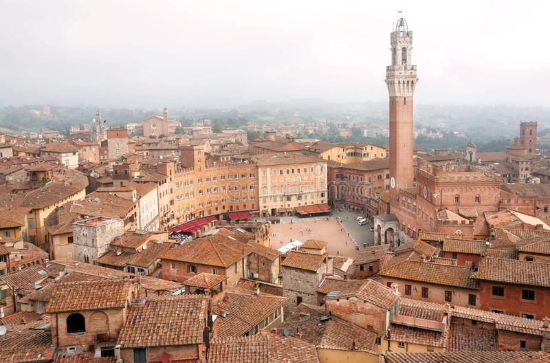Beautiful old buildings under morning mist in Siena, Tuscany. Tile roofs and 14th century tower Torre del Mangia, Italy. UNESCO World Heritage Site stock images
