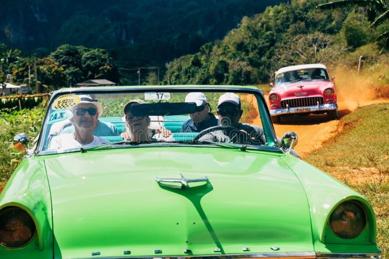 Beautiful old classic cars in Vinales, Cuba. 2 Beautiful old classic cars driving on a dirt road in Vinales, Cuba royalty free stock photo