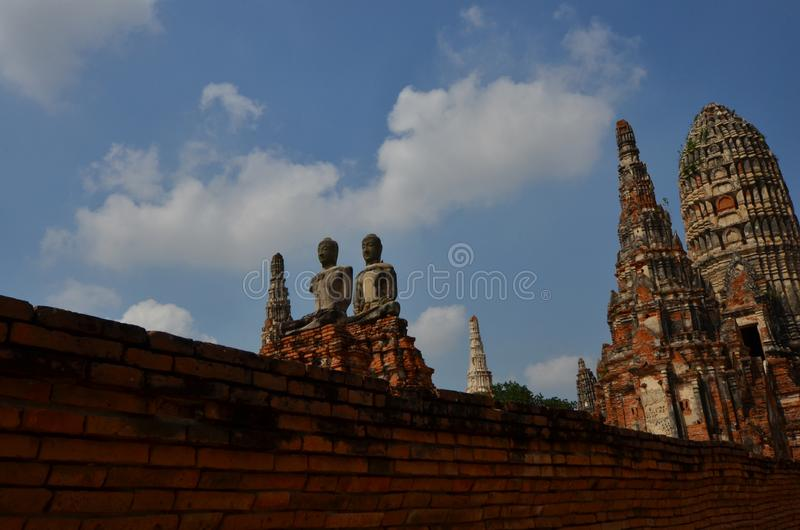 Old couple Buddha images and high pagoda on high floor. Beautiful old couple Buddha images with high pagodas and blue sky in Thailand royalty free stock photography