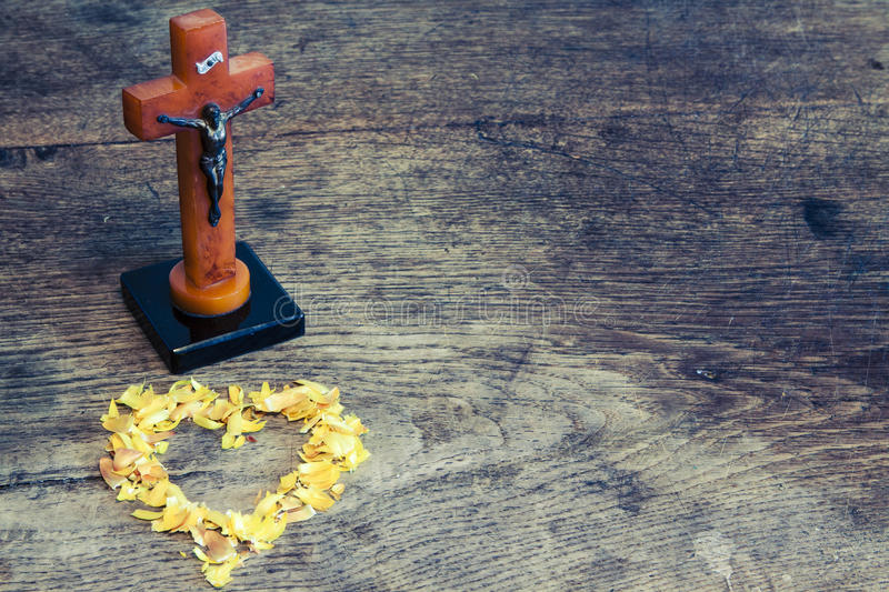 Beautiful old cross with jesus and heart from leafs on the old wooden floor royalty free stock images