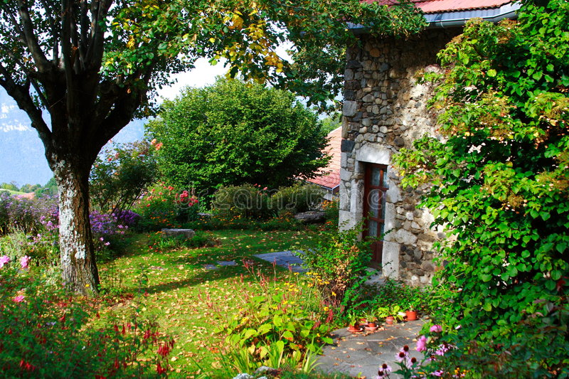 Beautiful old garden. Beautiful garden in the the french countryside with a typical stoned house royalty free stock photography
