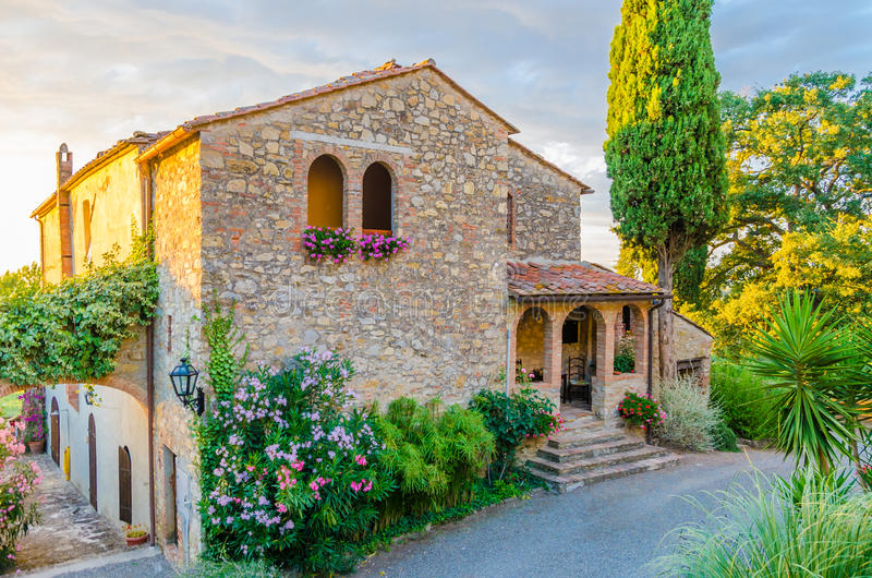 Beautiful old Itanlian stone house with arched windows and typical plants during sunset, Italy