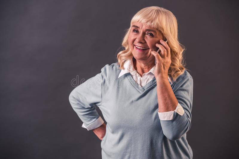 Beautiful old lady. In casual clothes is talking on the mobile phone and smiling, on gray background stock image