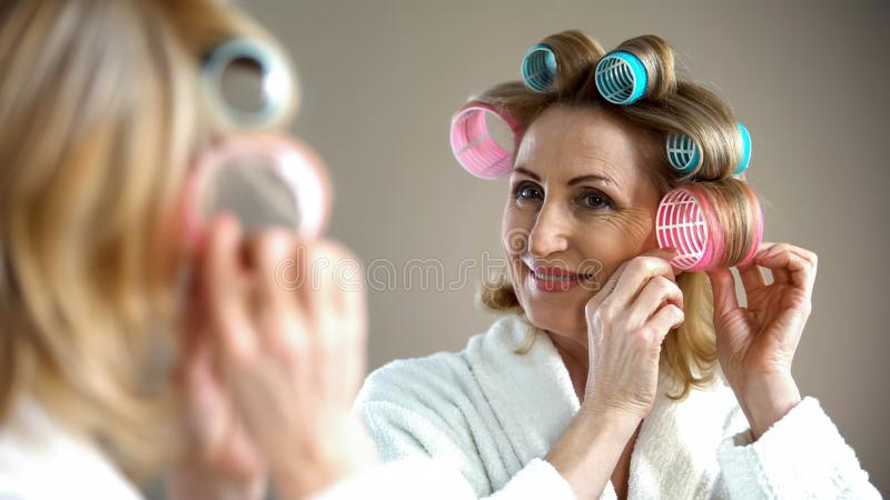 Beautiful old lady with curlers smiling into mirror, enjoying her look, beauty. Stock photo royalty free stock images