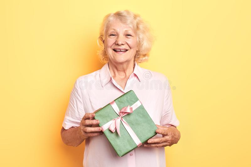 Beautiful old lady holding a gift box and smiling stock photos