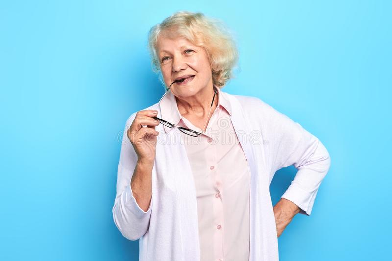Beautiful old lady in white lab coat holding glasses and loooking at camera stock images