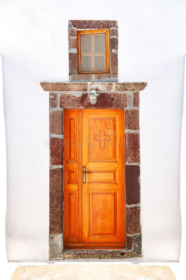 Beautiful old orange door on white facade of greek architecture, church, Santorini island, Greece, Europe. Beautiful details of. The island of Santorini. Famous stock photo
