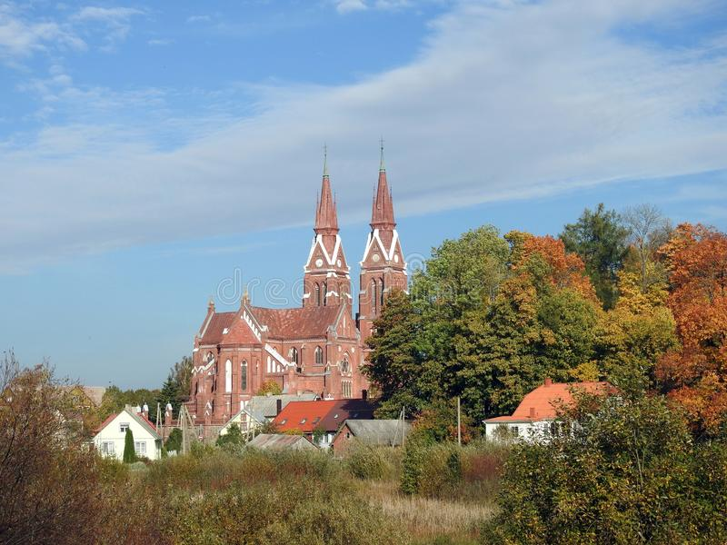 Old red Catholic church and homes, Lithuania royalty free stock photo