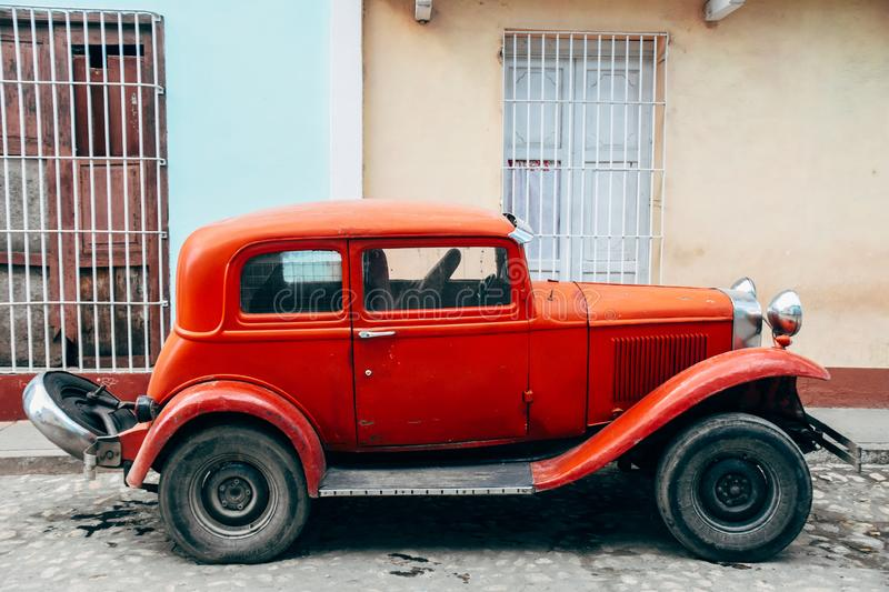 A beautiful old red classic car in Trinidad, Cuba. A beautiful old red classic car parked in Trinidad, Cuba royalty free stock images