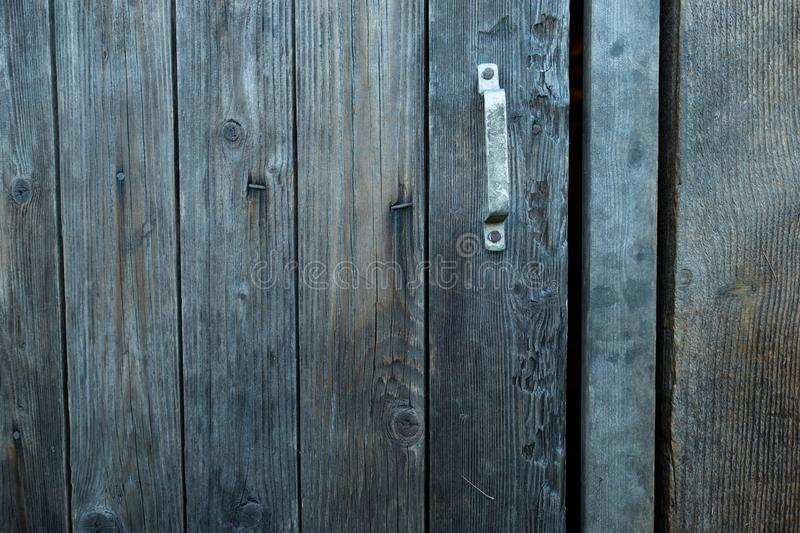 Beautiful old rustic wooden barn door with a handle. Close up stock image