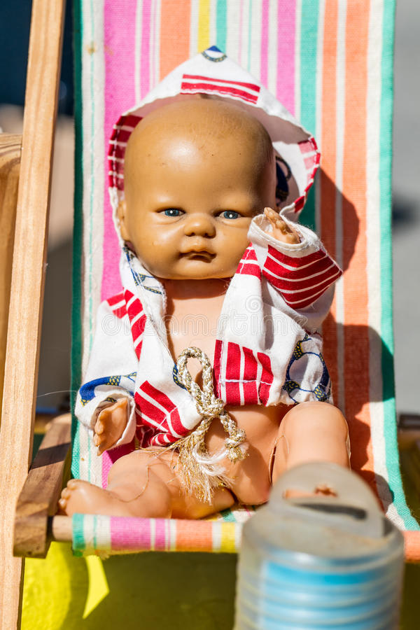 Beautiful old summer doll on small deckchair for childhood nostalgia. Display of a beautiful old summer doll on a small deckchair to recycle and reuse toys or royalty free stock images