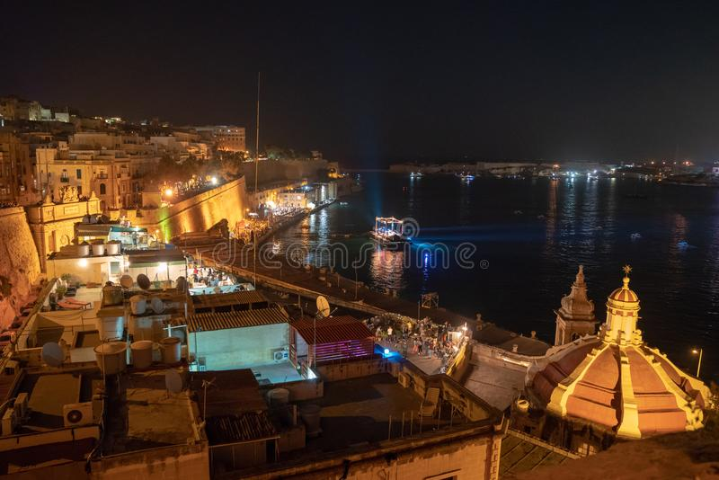 Beautiful old town of Valletta at night with many people crowded by the coastline watching live show and waiting for the fireworks. May 01, 2018. Valletta, Malta stock photo