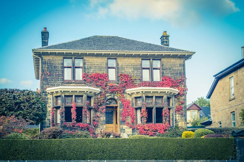 Beautiful, old traditional British house during Autumn, with autumnal leaves in front of it. stock image
