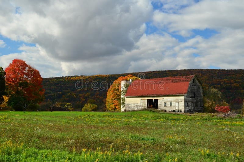 Beautiful old weathered barn on an upstate New York hillside in Autumn. Beautiful old weathered barn on an upstate New York hillside with fall foliage backdrop stock image