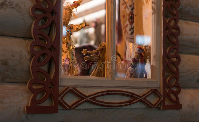 Beautiful old window in a wooden house with old traditional dolls. Beautiful old window in a wooden house On the window there are old traditional dolls From the royalty free stock images