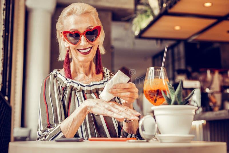 Beautiful old woman in funky sunglasses applying nourishing cream. Cheerful short-haired senior. Beautiful old woman in funky sunglasses applying nourishing stock image