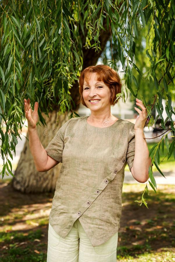 Beautiful old woman in linen retro vintage clothes pushing branches with leaves of willow royalty free stock image