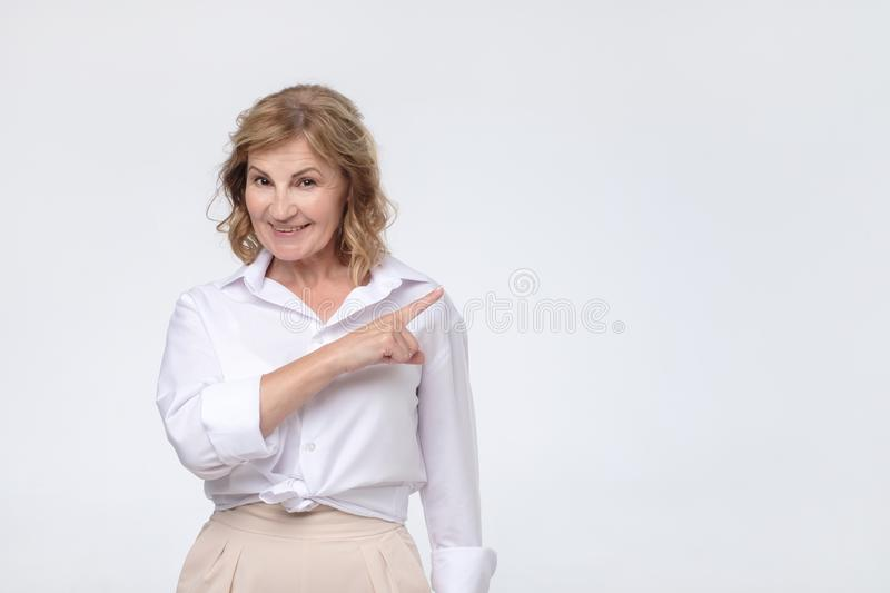 Beautiful old woman in white shirt is pointing to the side, looking at camera and smiling stock images