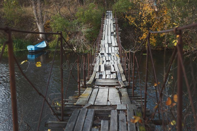 Old abandoned wooden bridge across river, dark background royalty free stock photography
