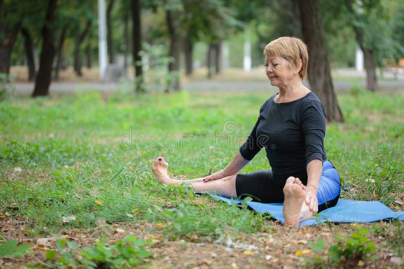 Beautiful old yoga woman. Mature lady on a mat on a park background. Healthy lifestyle concept. Copy space. stock photos