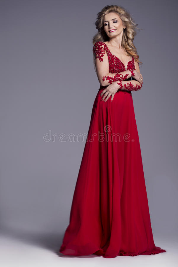 Beautiful older woman in an evening red dress royalty free stock photo