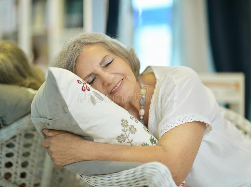 Beautiful older woman. Sleeping in the chair royalty free stock photography