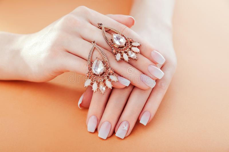 Beautiful ombre manicure with earrings. French nail design. Woman holding jewellery. Fashion concept. Beautiful ombre manicure with earrings. French nail design royalty free stock image