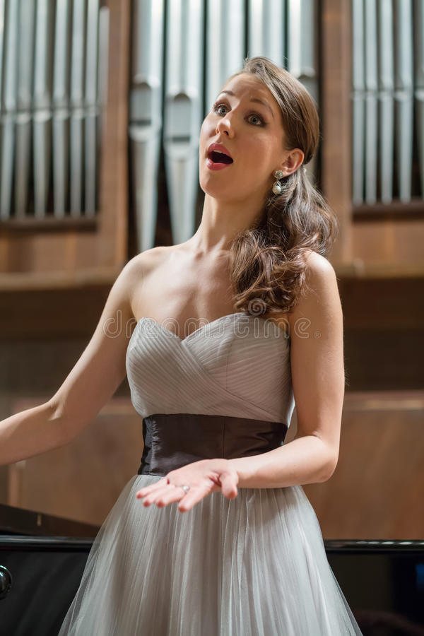 Beautiful opera singer sings. In the concert hall stock images