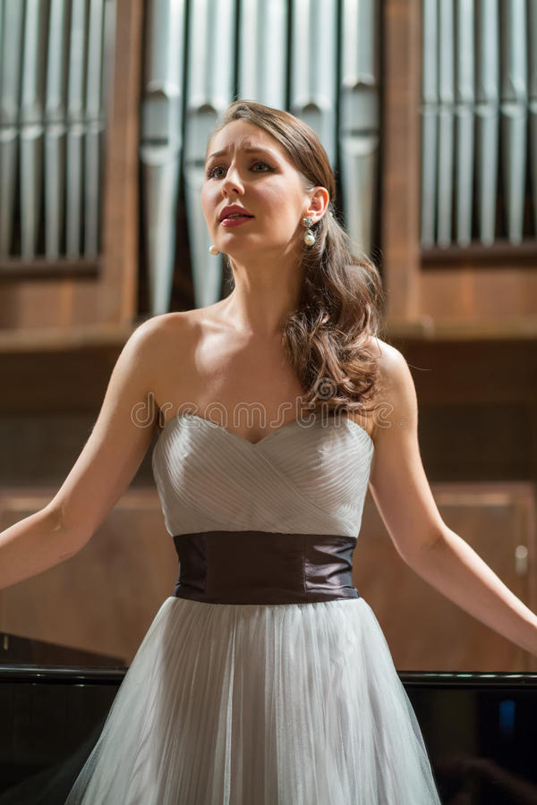 Beautiful opera singer sings emotionally. In the concert hall royalty free stock image
