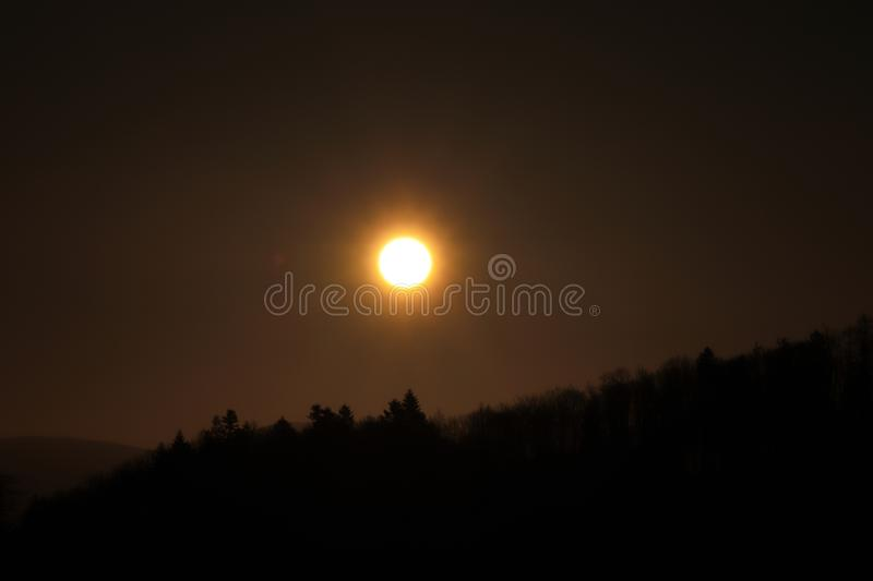 Beautiful orange ball on dark sky with shadows of trees. Sunset over black mountain. Eclipse of the sun in real time royalty free stock photos