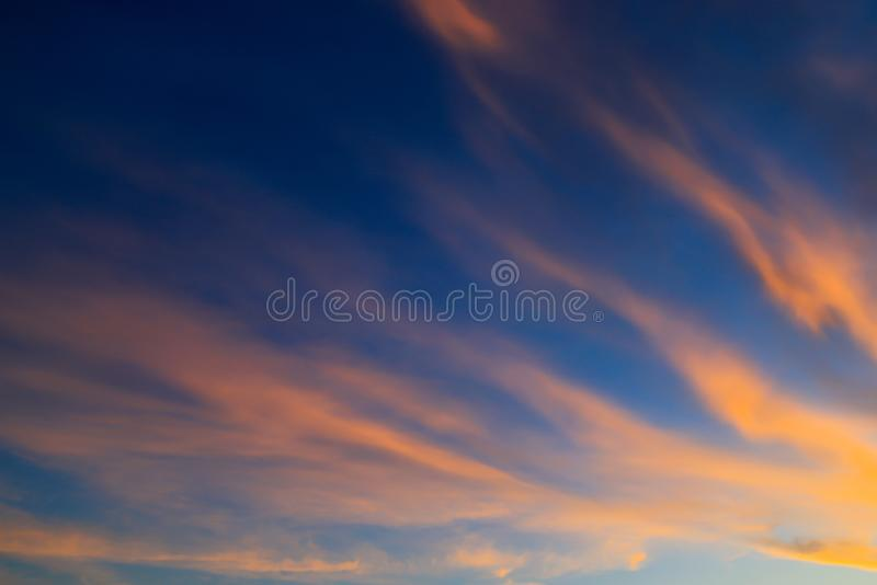 Beautiful orange feather clouds on a blue sky at sunset, magical background, autumn, spring, summer. Weather forecast royalty free stock photo
