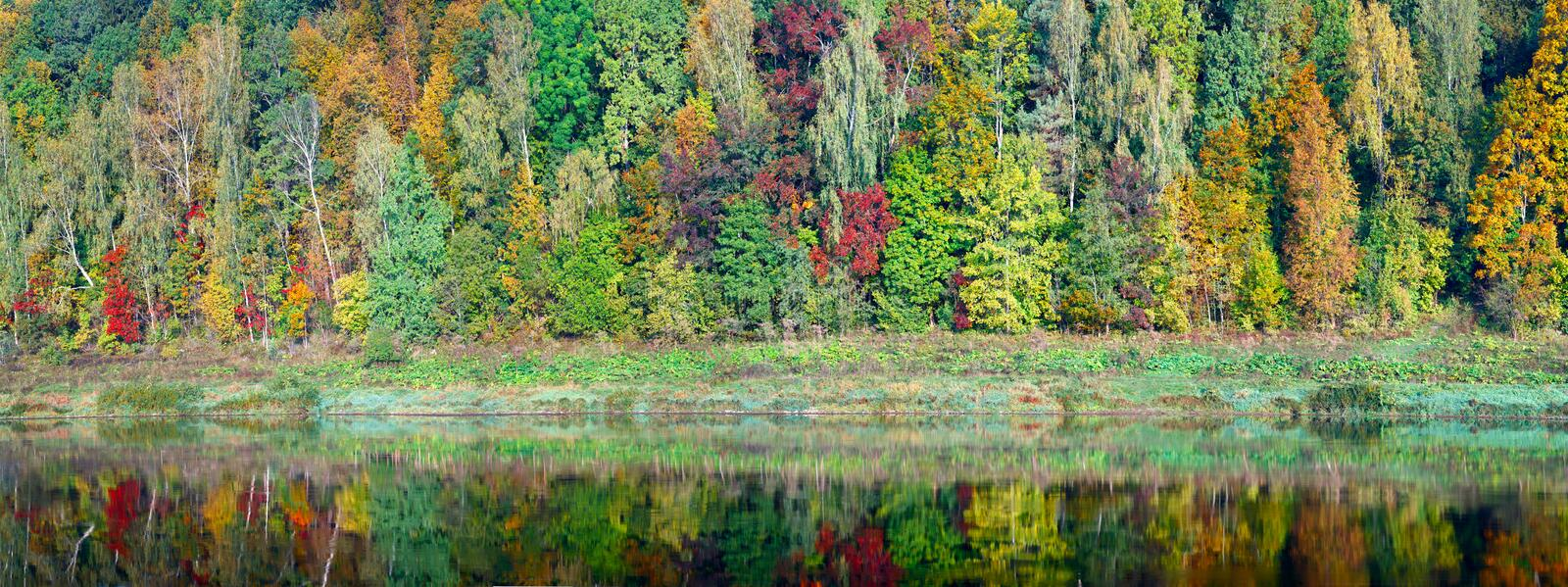 Beautiful orange, red and green autumn forest, many trees on the orange hills panorama reflection on water. Autumn background long stock photos