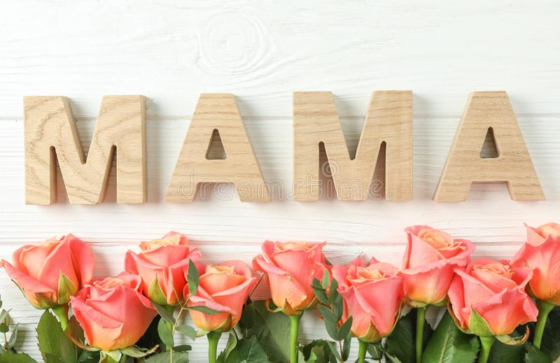 Beautiful orange roses and inscription Mom on white background stock images