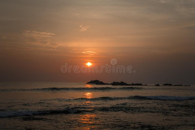 Beautiful orange sun at sunset and a path of light on the waters of the Indian Ocean. Beautiful orange sun at sunset and a path of light from the glare on the royalty free stock photo