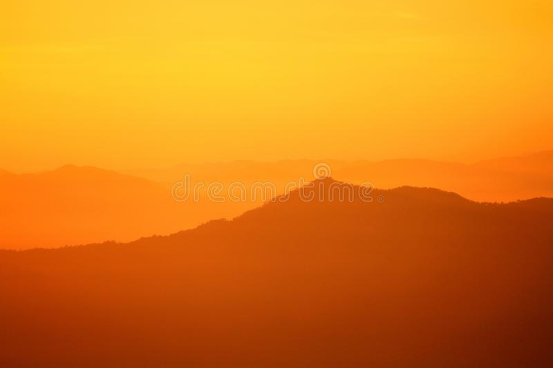 Beautiful orange sunlight or sunrise in morning with silhouette of big mountain for background royalty free stock photos