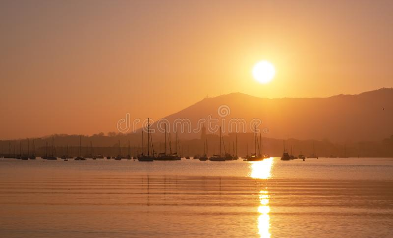 Beautiful orange sunset on the sea, silhouette of basque city in sunrise on seashore, peaceful landscape stock photos
