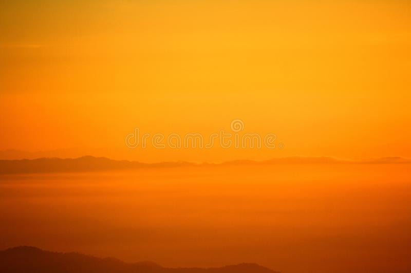Beautiful orange sunshine or sunrise in morning with silhouette of mountain for background stock photos