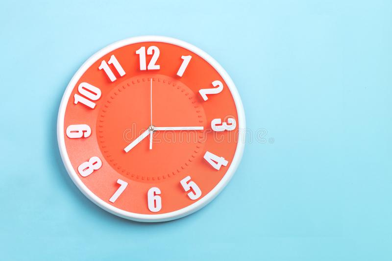 Beautiful Orange wall clock on blue background ,concept of Start the morning to work stock photo