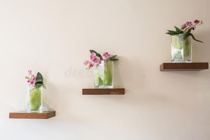 Beautiful orchid in glass vase on shelf. royalty free stock photo