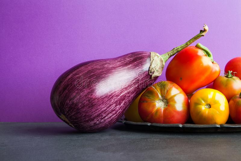 Beautiful organic violet eggplant and fresh vegetables harvest on a vintage tray. Ripe bell pepper, yellow red tomatoes stock images