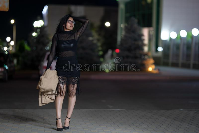 Brunette girl poses against the evening night city, colorful lights illuminate the shopping windows. A beautiful oriental girl from Turkmenistan in the evening royalty free stock images