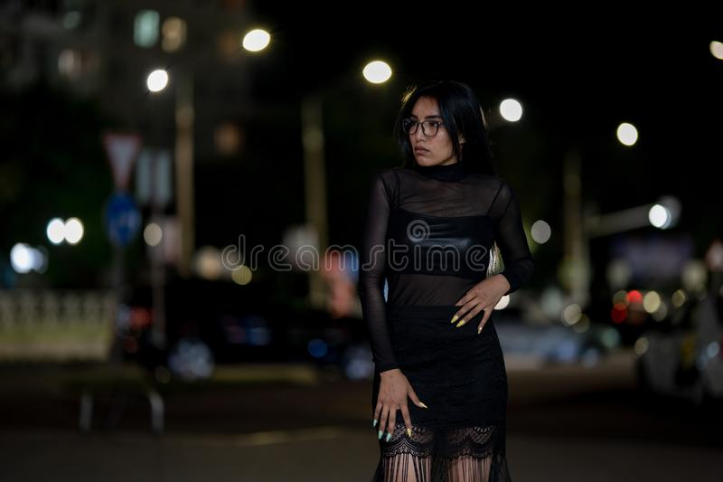 Brunette girl poses against the evening night city, colorful lights illuminate the shopping windows. A beautiful oriental girl from Turkmenistan in the evening stock images