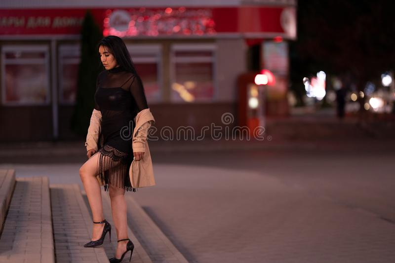 Brunette girl poses against the evening night city, colorful lights illuminate the shopping windows. A beautiful oriental girl from Turkmenistan in the evening stock image