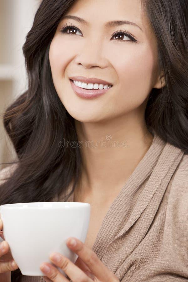 Beautiful Oriental Woman Drinking Tea or Coffee stock images
